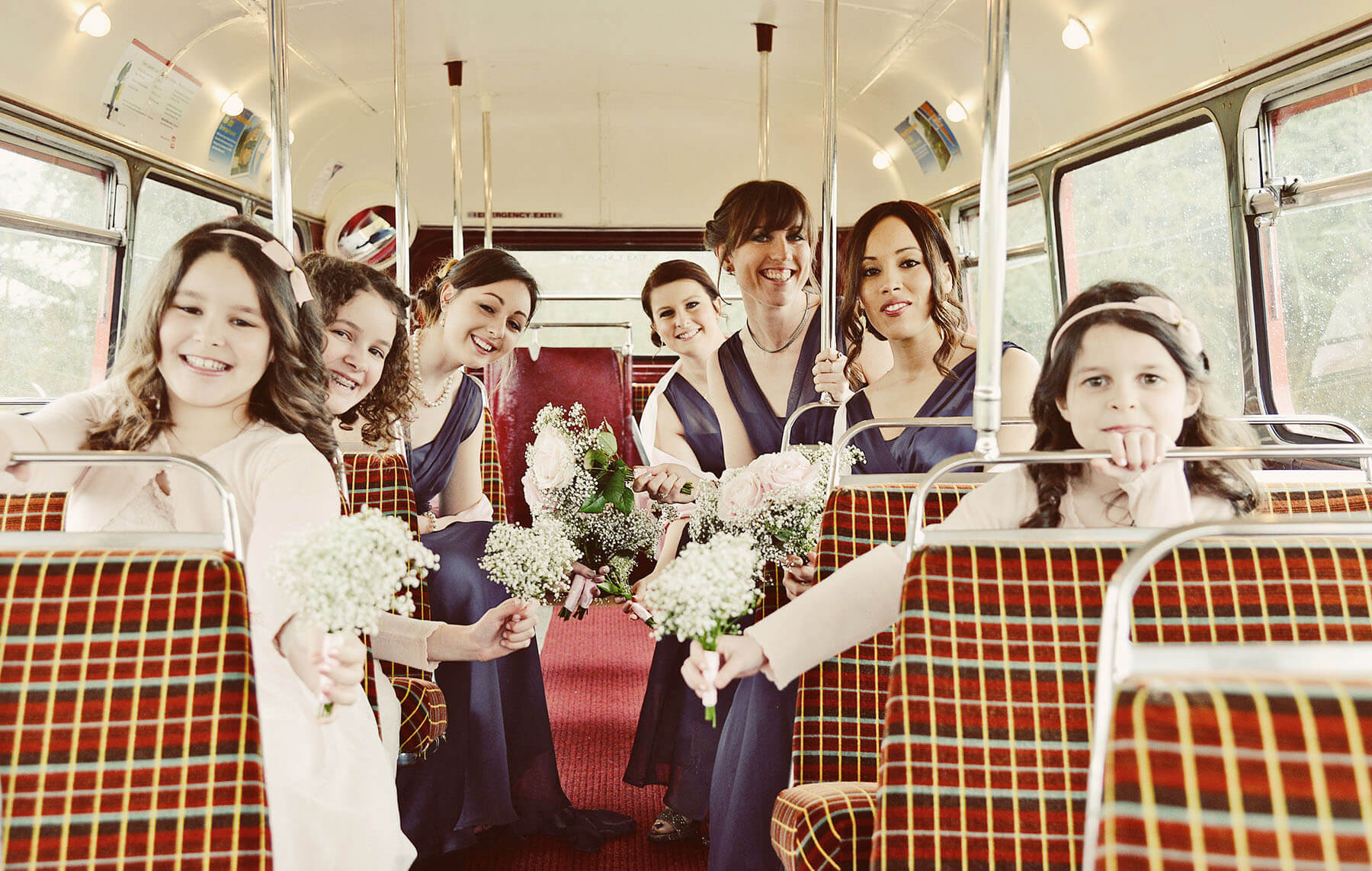 Bridal party sitting on a vintage London bus holding bouquets of flowers