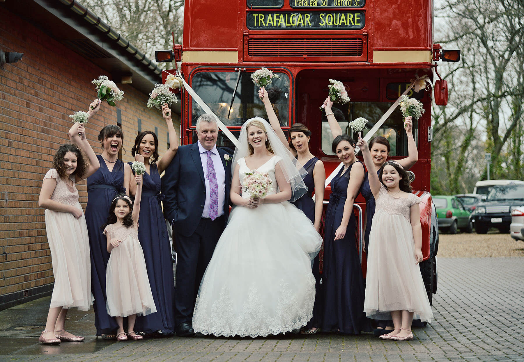 Bride with father and bridal party stood in front of a London bus holding bouquets on wedding day