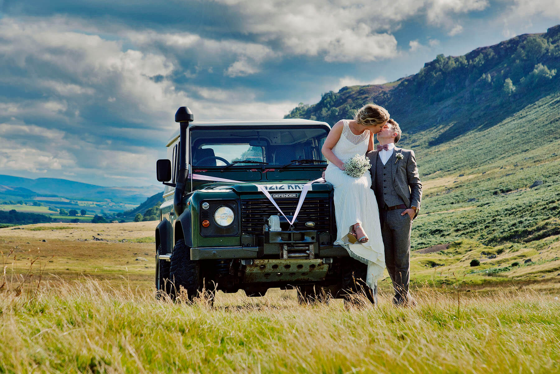 Bride and groom sitting on a Land Rover kissing in the Lake District, Cumbria
