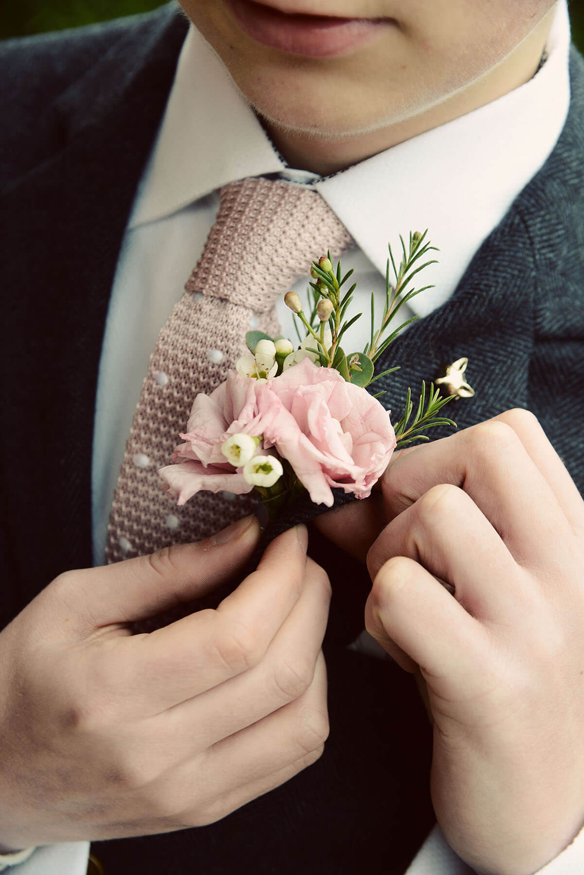 Male wedding guest attaching a rose to his suit jacket