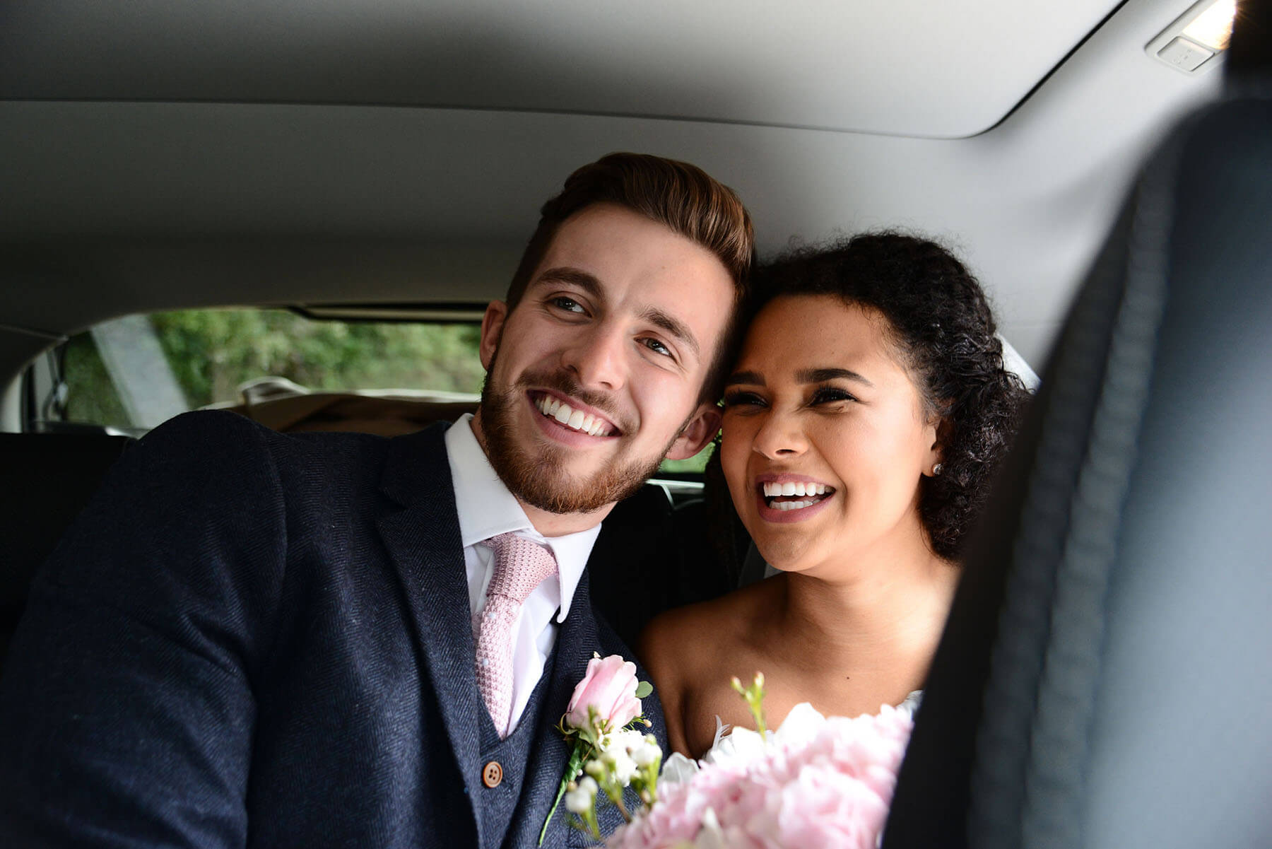 Bride and groom smiling in the back of the wedding car