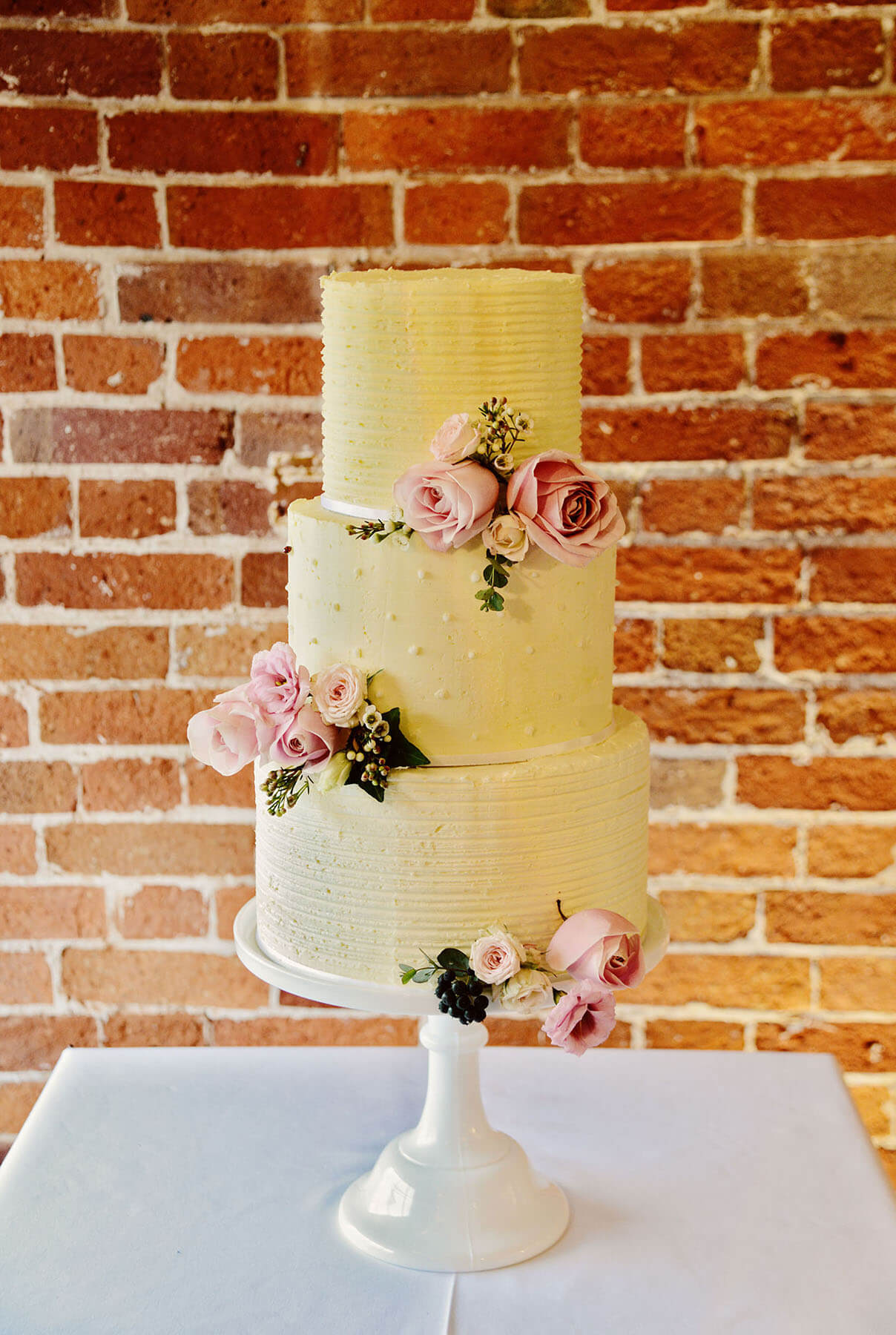 Cream wedding cake with roses on a white stand