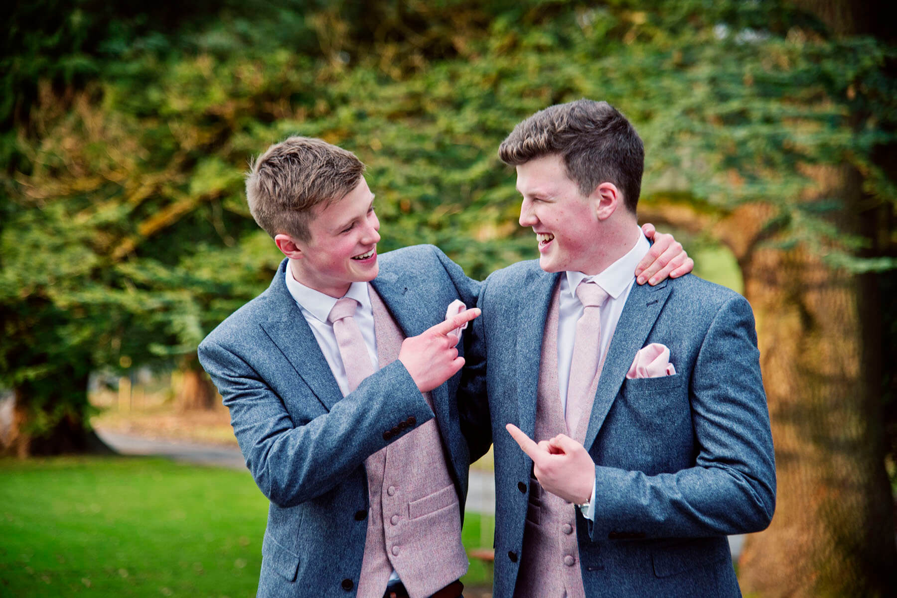 Groom and best man laughing and pointing at each other with trees in the background