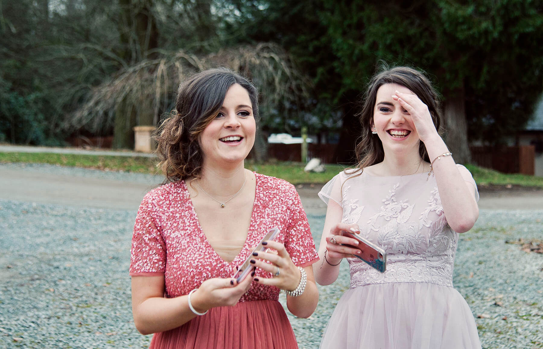 Two female wedding guests laughing with phones in their hands