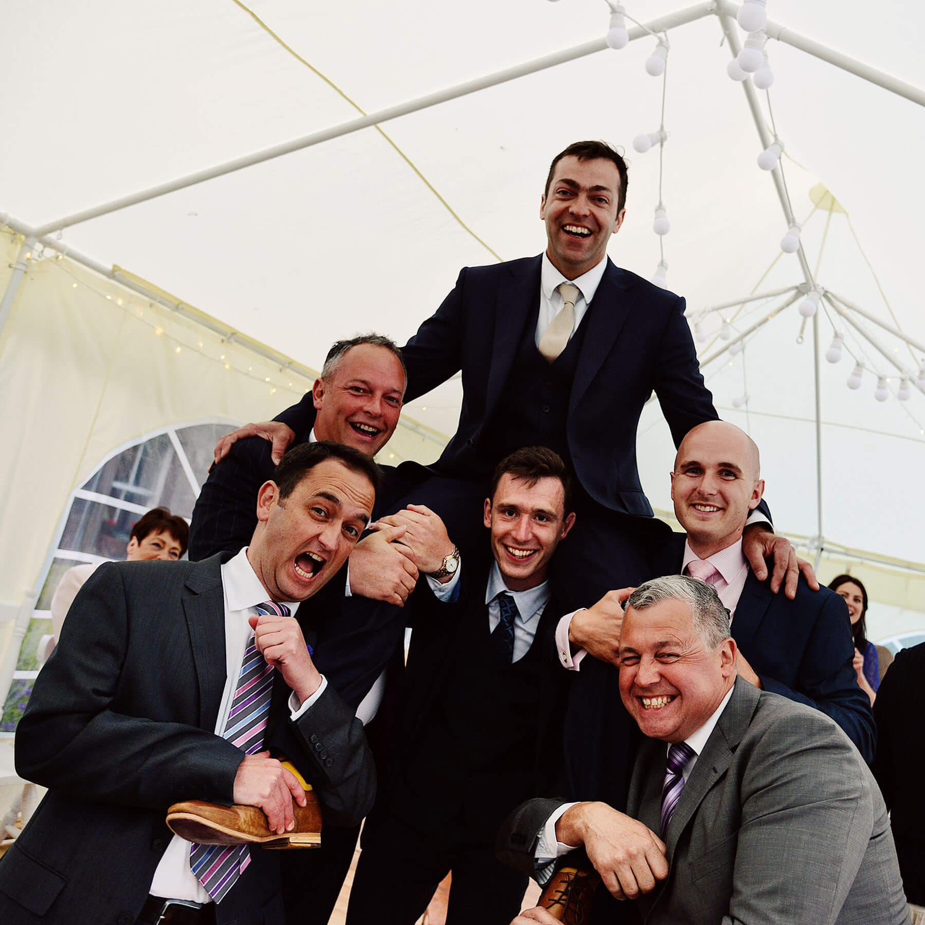 Groom on the shoulder of a friend and surrounded by friends in a marquee at the wedding reception