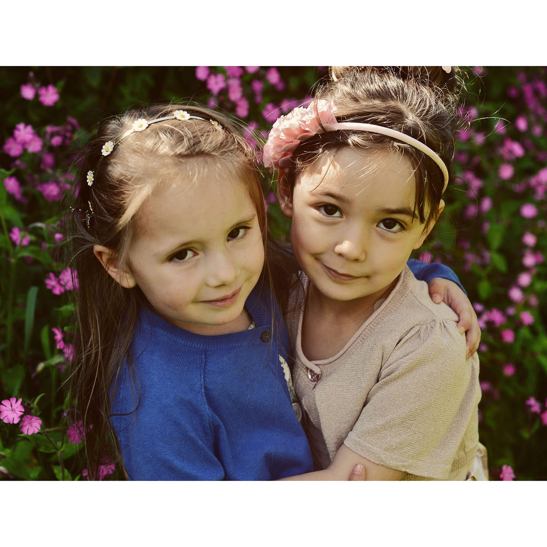 Two young girls hugging with pink flowers in the background