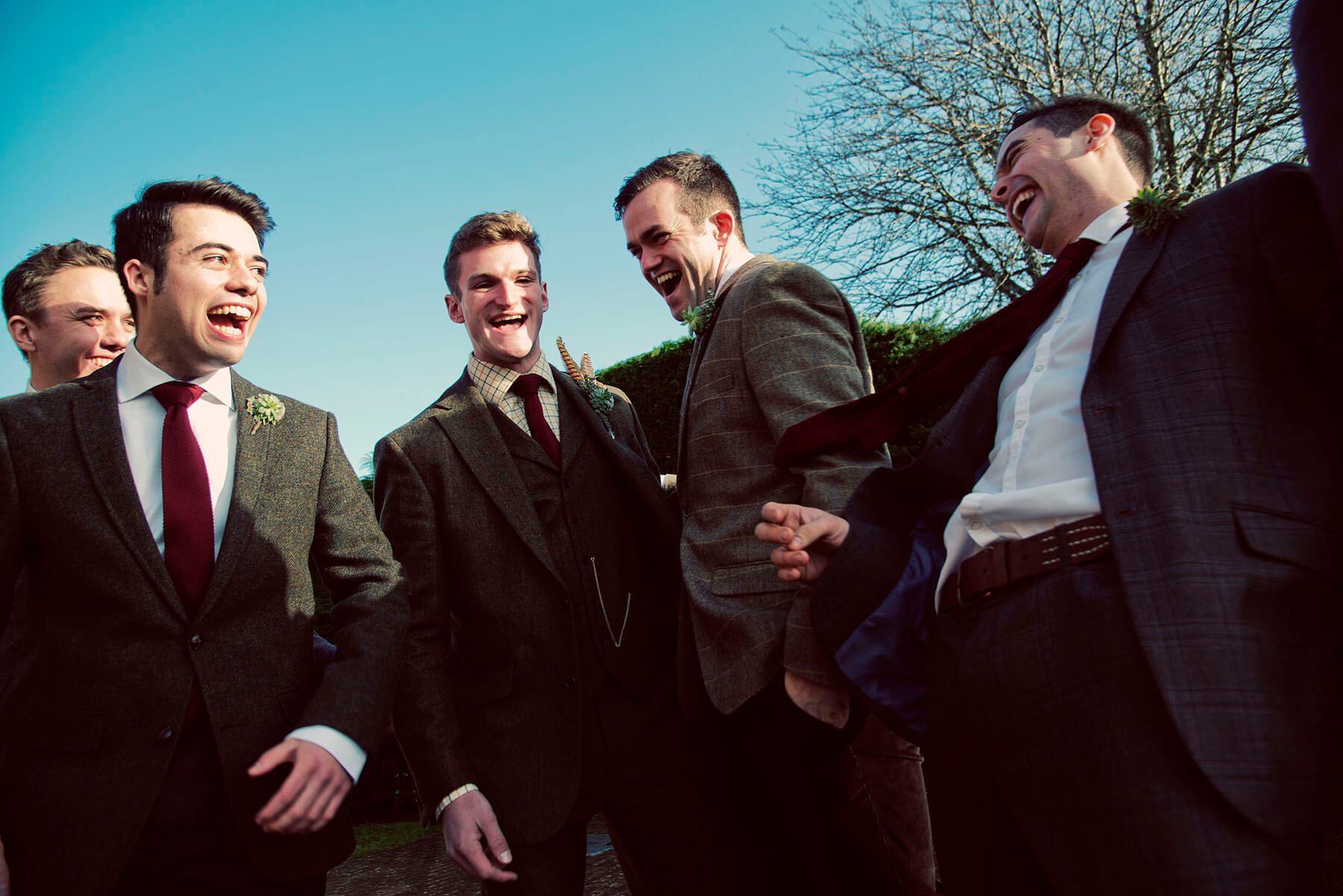 Groom and friends laughing together outside