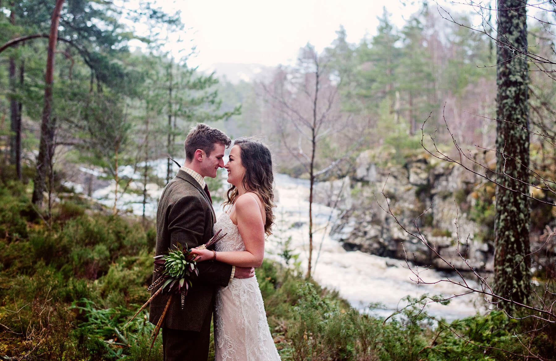 Bride and groom facing each other in front of a river in Cumbria