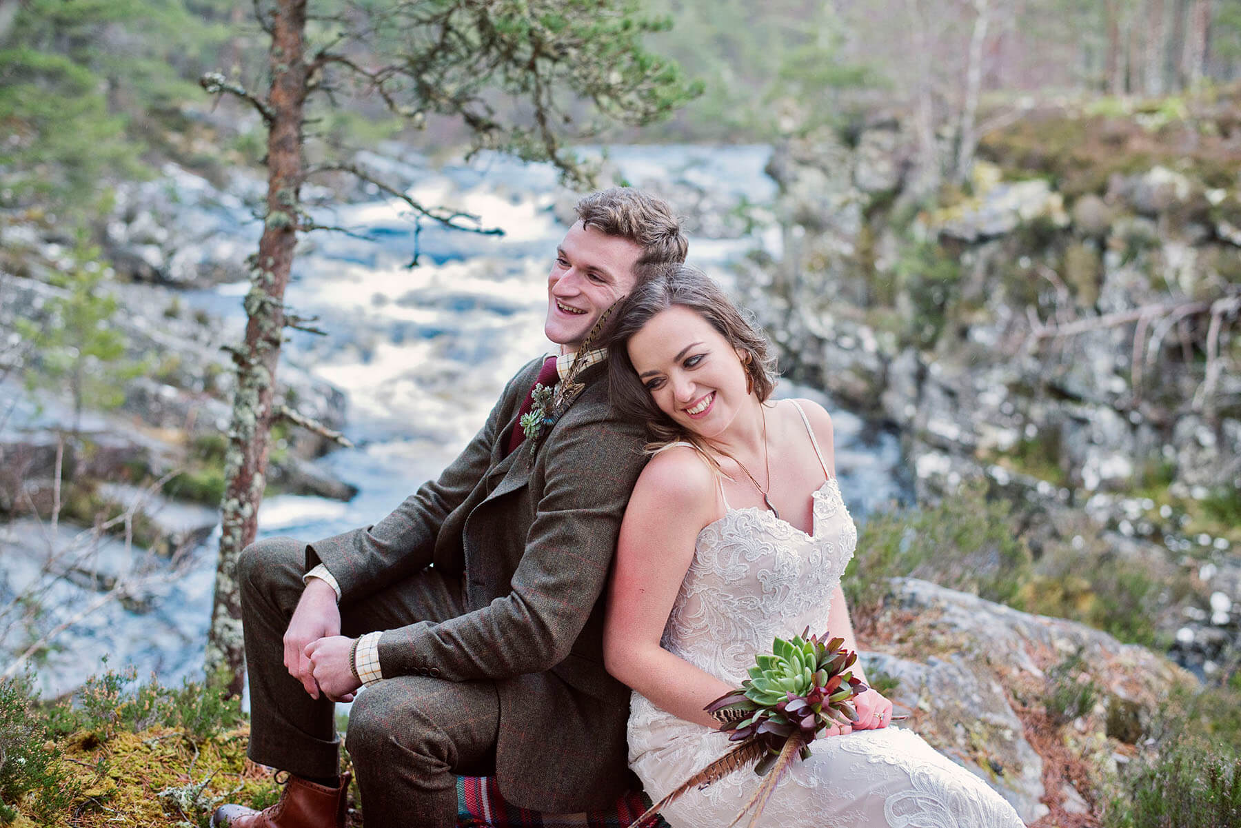 Bride and groom laughing sitting on a rock in front of a river in Cumbria