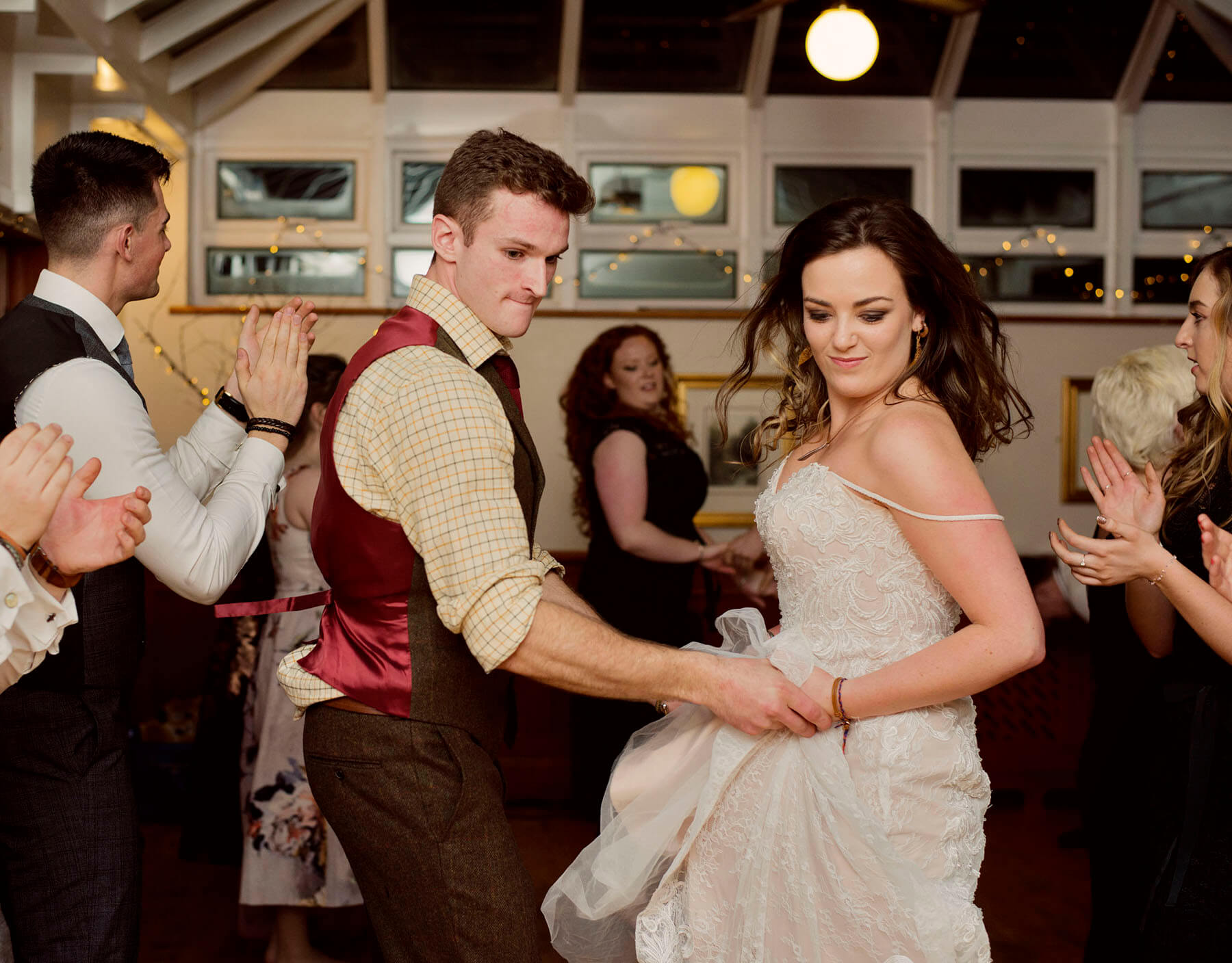 Bride and groom dancing a ceilidh holding hands