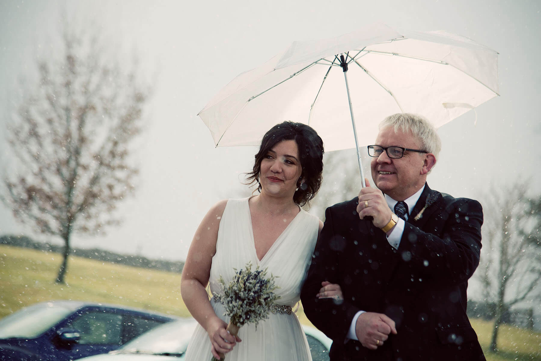 Bride with father under an umbrella in the Cumbrian countryside
