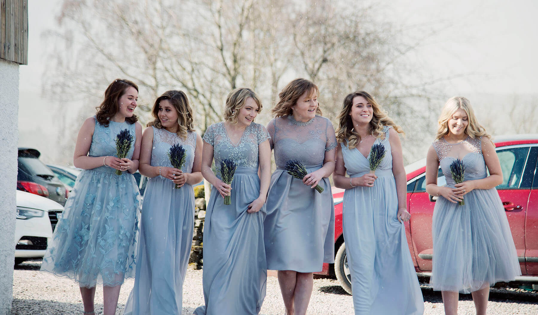 Bridesmaids walking in a row holding bouquets