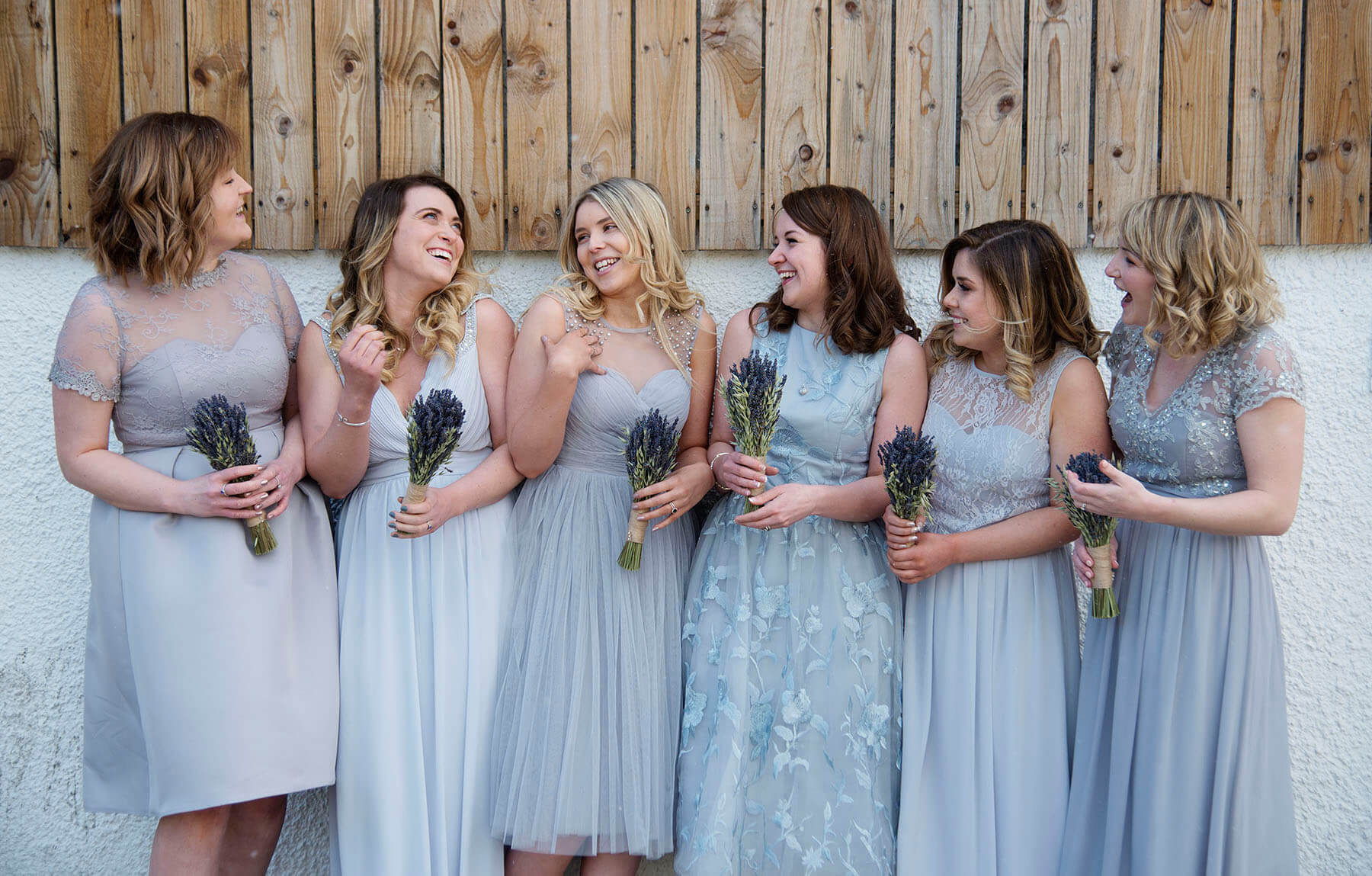 Bridesmaids stood in front of a wall holding bouquets and laughing