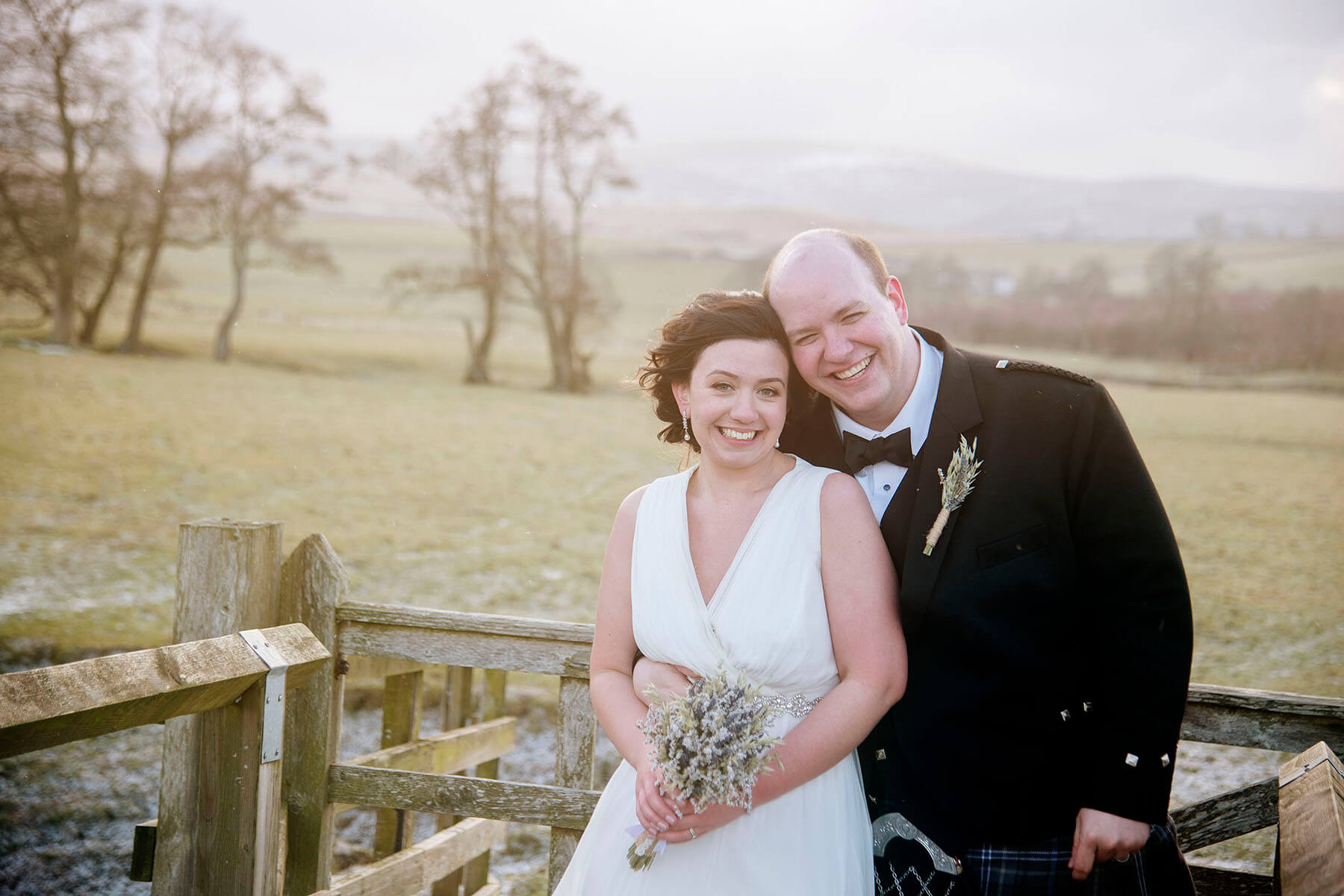 Bride and groom stood in front of Cumbrian landscape