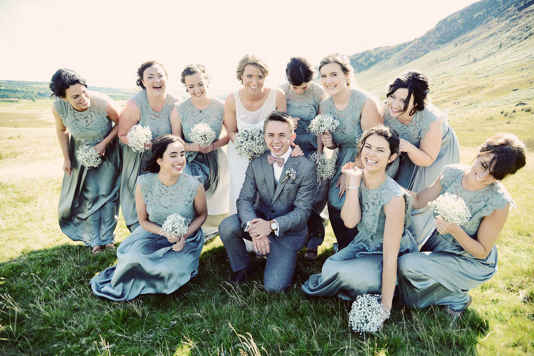 Bride and groom surrounded by bridesmaids on a mountainside in the Lake District