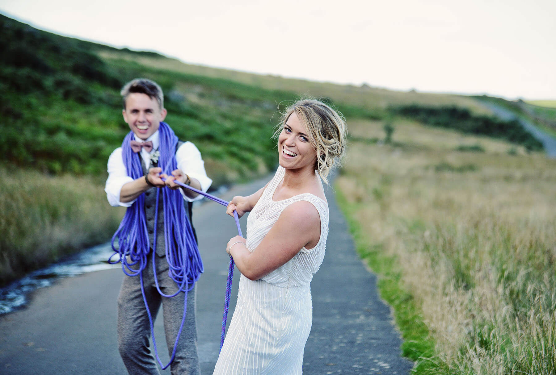 Bride and groom pulling some climbing rope and laughing on a countryside road