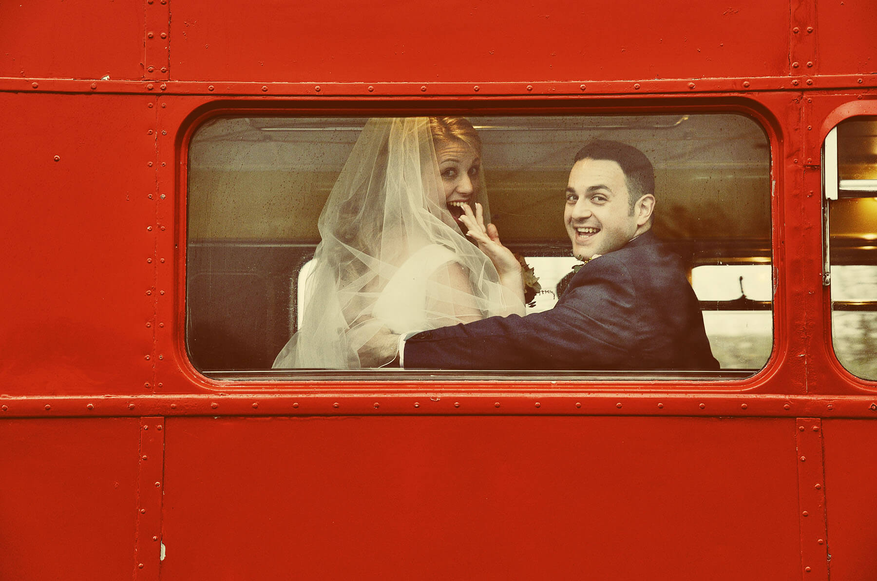 Bride waving and groom looking out of the back window of a red London Bus